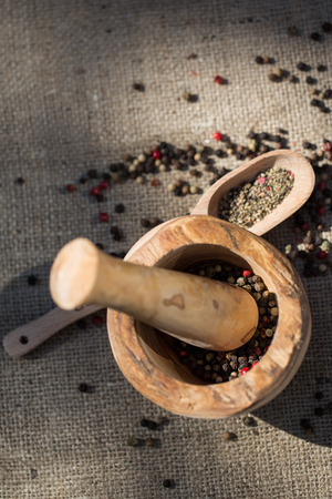 ecru: Different types of pepper on wooden spoon and in mortarin sunny day lights
