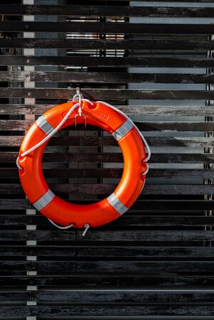 Orange lifebuoy in sea port