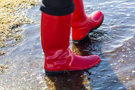 Walking  through puddles in wellies in sunny weather Stock Photo