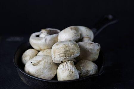 cast iron pan: White mushrooms close up on cast iron pan