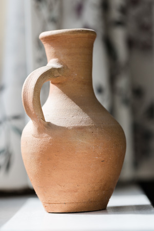 Jarrón de cerámica antigua de barro junto a la naturaleza muerta de la ventana Foto de archivo