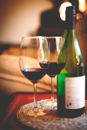 Bottle of red wine with two glasses on red table in dark romantic room candle light Stock Photo