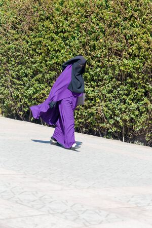 emigranti: Islamic Muslim woman wearing violet black Niqab walks on Marrakesh street. 15 February 2017