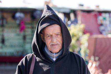 Poor Morrocan old man portrait. Wearing traditional hooded cloak. Roadside vendor selling cheap goods. Seen on 16 February 2017 outside of Marrakesh