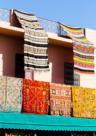 Handmade colorful carpets and rugs hanged on balcony African house in Marrakesh Morocco
