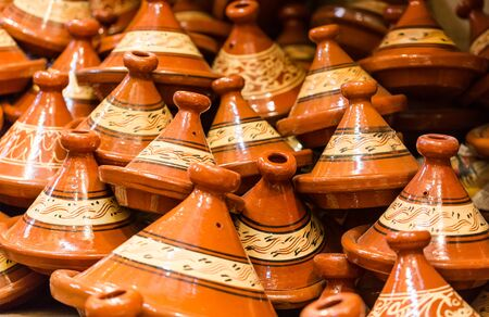 Handmade brown clay tajins for food steaming arranged in rows ready for sell in Marrakesh, Morocco