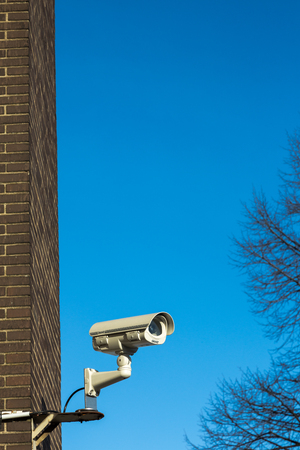 voyeur: CCTV video camera on private property recording surroundings. Close up vertical shot with brick wall and blue sky in background Stock Photo