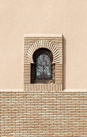 Arabic style windows in Marrakesh. Front elevation view on typical Morocco architecture. Vertical full frame crop Stock Photo