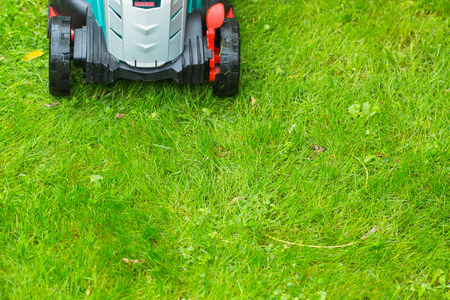 cutter: Cordless battery power lawn mower close up on green grass background. Full frame horizontal composition.