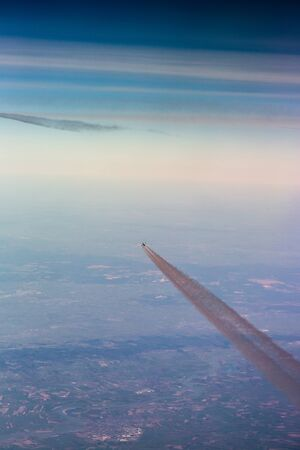Jet fast flying in sky over Europe with grey chemtrails view from top. Vertical full frame crop with clear blue sky