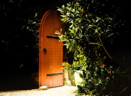 Old wooden heavy open door as entrance to the fairy tale. Garden at Arundel Castle in UK