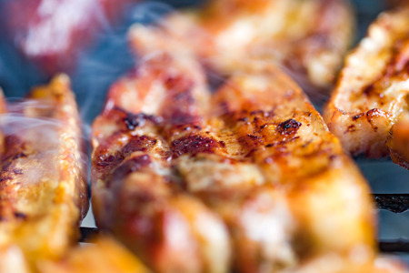 tummy time: Grilled pork belly, bacon, on hot traditional charcoal bbq close up. Horizontal macro shot