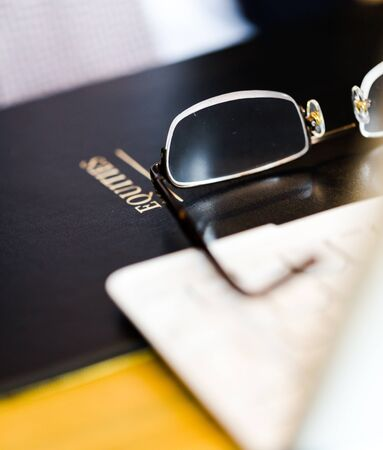 Equity black holder on esk with glasses and laptop. Vertical close up composition with shallow deep of depth