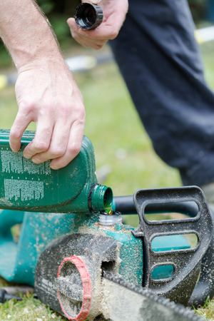 replenishing: Handyman replenishes the oil in chain saw for chain maintenance