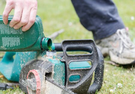Handyman replenishes the oil in chain saw for chain maintenance