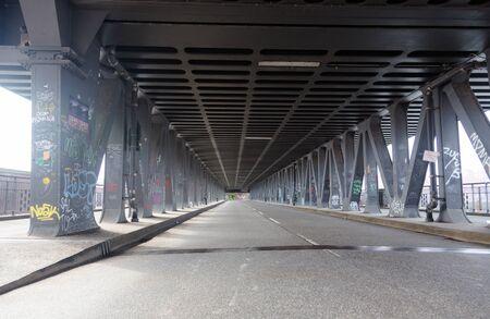 Empty road under steel bridge in industrial area in Hamburg, Germany. Low wide angle perspective. Horizontal crop