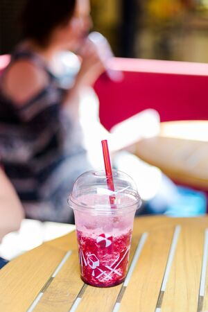 Iced cold milk shake in plastic cup with straw on table in coffee shop. Blurred young adult woman in background drinking a strawberry shake. Vertical, day light, close up, color photography Stock Photo