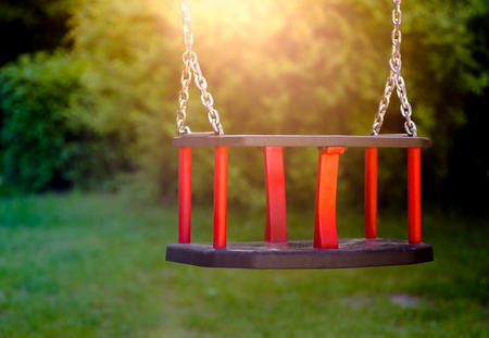 Old vintage wooden red teeter in sunset light. Horizontal crop, close up and focus on swing Stock Photo