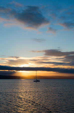 estereotipo: Sailboat with fallen sails in sunrise light on full North Sea in Weymouth Bay at Weymouth coast. Vertical composition with sailboat in center on low horizon