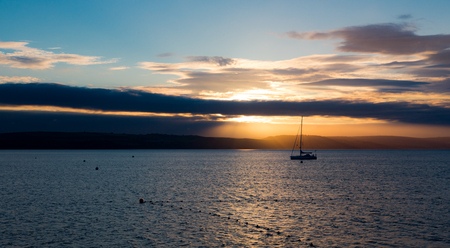 Sailboat with fallen sails in sunrise light on full North Sea in Weymouth Bay at Weymouth coast. Horizontal composition with sailboat in center and low horizon Stock Photo
