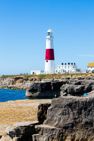 Portland Bill Lighthouse on Portland rocks in sunny summer day with blue clear sky. Vertical full frame orientation. View from east side Stock Photo