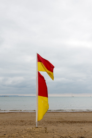 border patrol: Red and yellow lifeguards flag on beach. Dramatic sky with clouds in backgrounds. Stock Photo