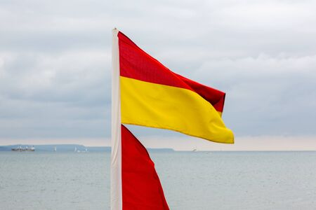 Red and yellow lifeguards flag on beach. Dramatic sky with clouds in backgrounds. Stock Photo