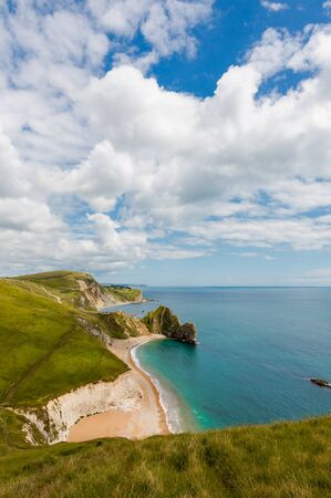 Durdle Door, Dorset touris attraction view from west side. Sunny afternoon light with clouds on blue sky and azure sea. Stock Photo