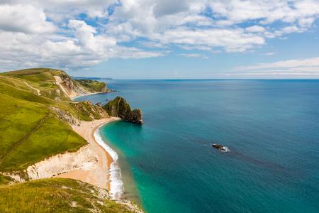 Durdle Door, Dorset touris atrakcją widok od strony zachodniej. Sunny popołudnie światło z chmurami na niebieskim niebie i lazurowym morzu.