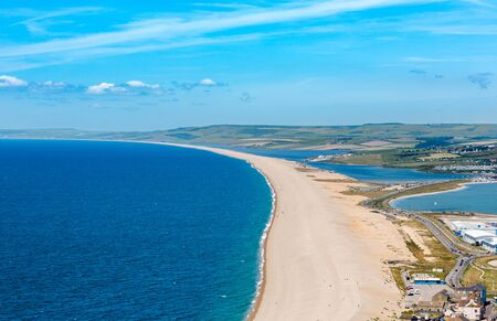 Aerial view on Chesil Beach on Isle of Portland, UK. Horizontal crop, high horizon in sunny summer day, blue sky and azure sea. Stock Photo