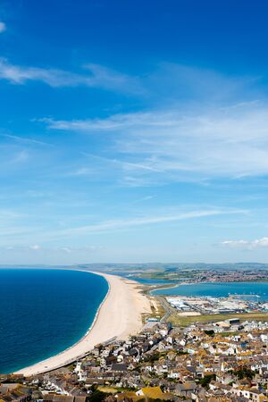 Aerial view on Chesil Beach, marina and Fortuneswell town on Isle of Portland, UK. Vertical crop, low horizon. Sunny day, blue sky and azure water Stock Photo