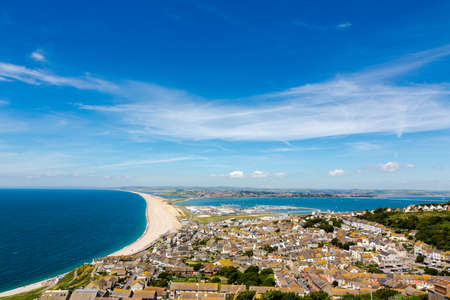 english countryside: Aerial view on Chesil Beach, marina and Fortuneswell town on Isle of Portland, UK. Horizontal crop, low horizon. Sunny day, blue sky and azure water