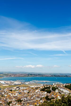 english countryside: Aeial view on marina ad Fortuneswell on Isle of Portland. Bue clear sky, azure water, low horizon. Vertical crop