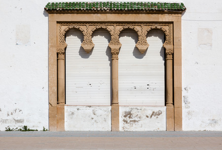 concealment: Decorative site with columns and closed shutters. Traditional Moroccan architecture in Essaouira, Morocco. Horizontal straight view