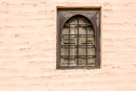 concealment: Old wooden rustic closed window with metal lattice in traditional muslim house in Morocco. Horizontal direct view