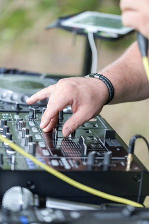 Dj works on mix console at outdoor party. Close up shot, focus on urn buttons and dj hands. Stock Photo