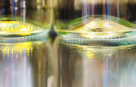 White wine bottles on glass table with bottles reflection. Macro crop background. Full frame horizontal shot. Stock Photo