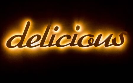 Delicious banner word with low back ight hanged on wall. Horizontal dark background with bright word
