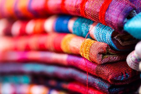 Colorful, vibrant red, blue, purple scarfs for sale on traditional medina souk. Macro crop shallow depth of field horizontal orientation