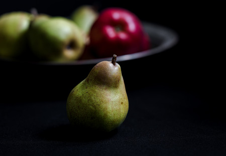 Red apples, green pears and yellow quinces on dark background. Juice autumn fruits still life photography. Close up shot with selective focus and shallow depth of field.