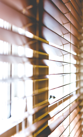 Wooden window blinds partially closed with bright light going through. Close up detailed crop, side angle perspective, shallow depth of field