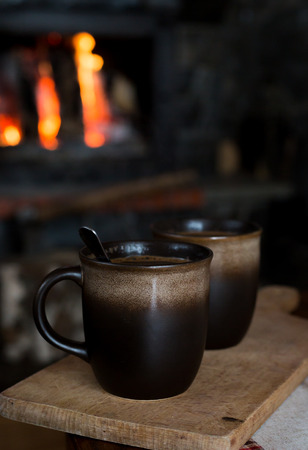 Old clay mug of coffee with a spoon on wooden vintage chopping board at fireplace in cold day. Selective foreground focus on cup with blurred fire background
