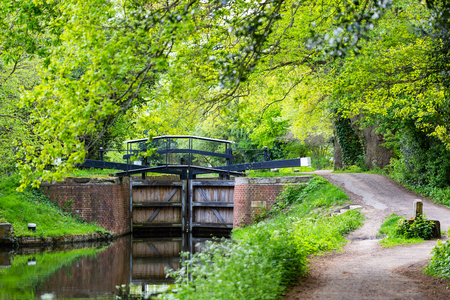 Water gates on Bansigstoke Canal at walkpath in Goldsworth Park near St John village in Woking, Surrey. Spring time with green trees aroundm sunny day.