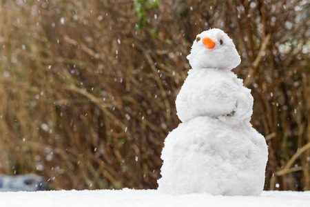 Snowman in garden on blurred bush background with fallen snowflakes. Low angle, close up crop Stock fotó - 119363735