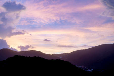 Sun setting during blue hour over hills and mountains 免版税图像