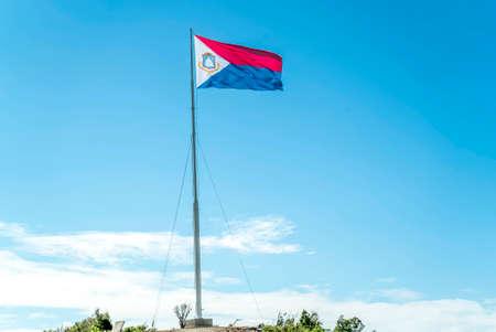 St.maarten flag flying high on top of a hill 免版税图像