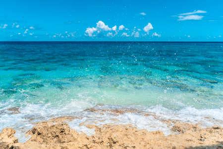 Blue sea water clashing on beautiful beach coast.
