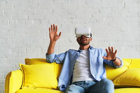 Front view of young smiling man using virtual reality glasses and showing his hand up while sitting on yellow sofa. 3d technology, entertainment, cyberspace concept 免版税图像