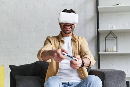 Young smiling man in VR headset playing video game with joystick, siting on the couch