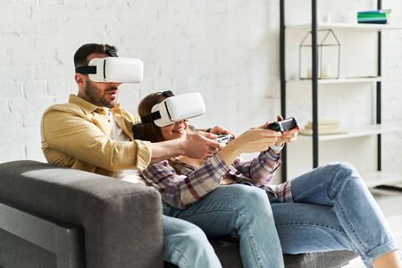Young smiling couple in VR glasses playing video game with joystick, siting on the couch